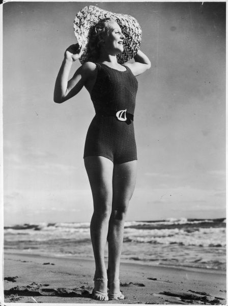 A woman in a boyish tank style swim-suit with a ship design belt buckle, and wearing a magnificent wide-brimmed hat, admires the view out to sea