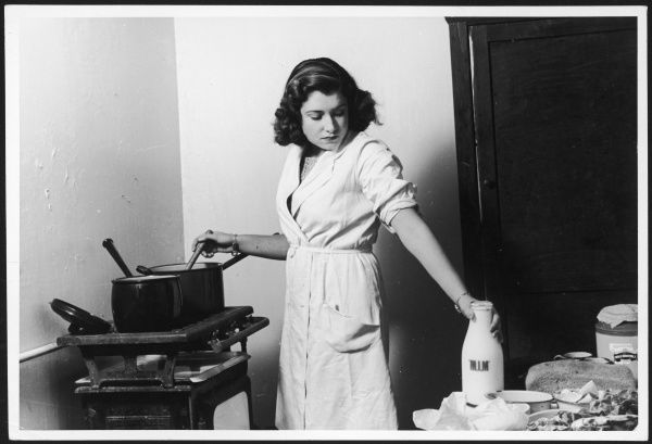 A housewife cooks on a simple stove in a bare and austere kitchen, adding milk to the pan she is stirring