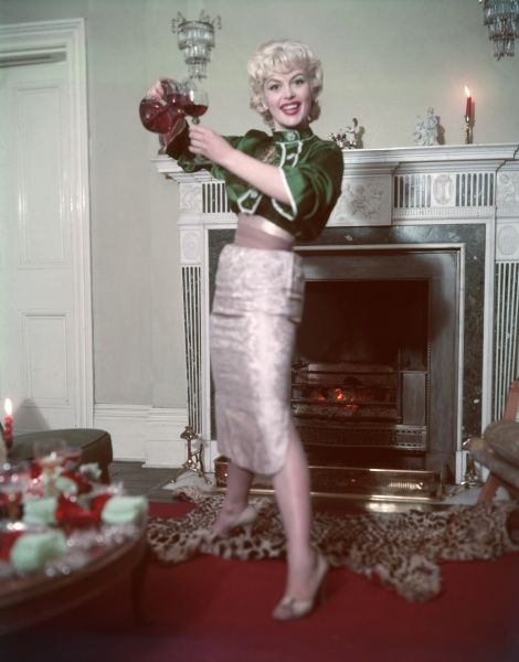 Gleeful blonde model, wearing an orientally inspired ensemble of silver pencil skirt with side splits & green silk blouse with mandarin collar, pours herself a drink