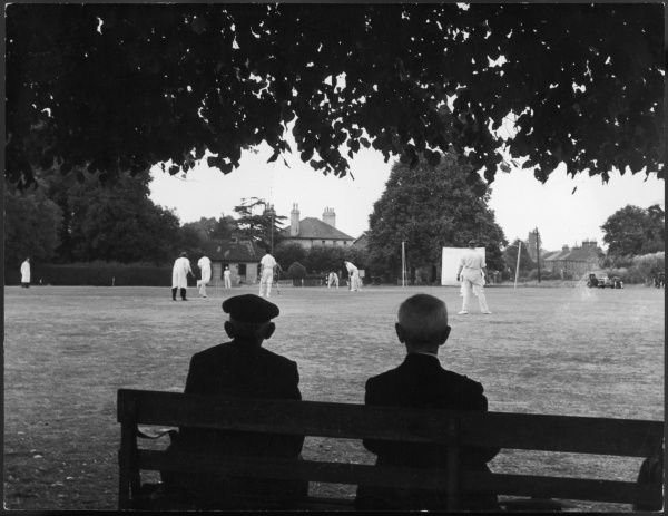 Two men sit on a bench in the shade to watch a cricket match in Kent