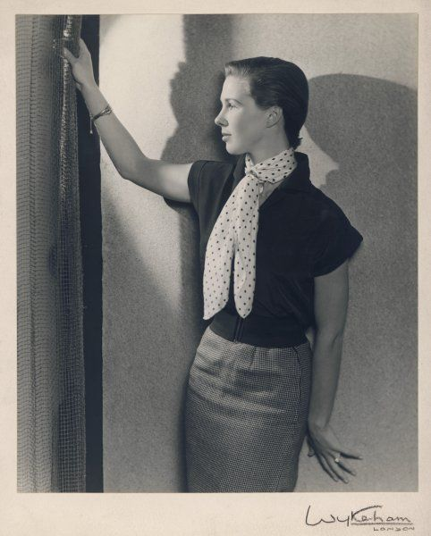 A young woman with a very short hair-cut, wearing a pencil skirt, cap-sleeved blouse and wide elasticated belt stands in profile against a wall
