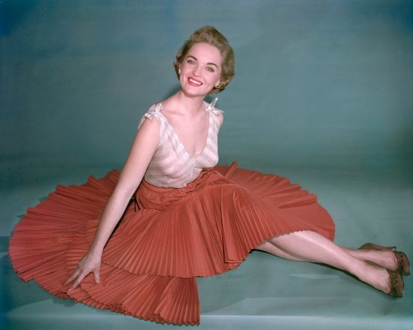 A smiling model poses and shows off her legs wearing a sunray pleat skirt and chevron striped sleevelss top