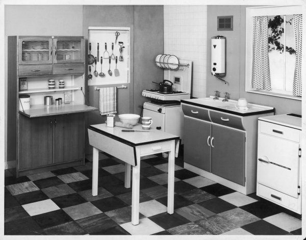 A classic kitchen, with a dresser, folding table, gas cooker with whistle kettle, trendy floor tiles and various types of kitchenalia