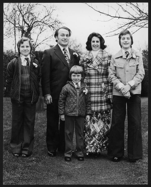 A family with three young sons photographed wearing carnations at a wedding. Date: 1970s