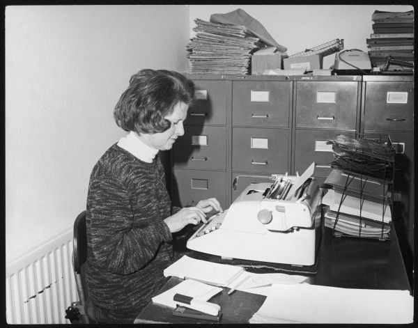 A typist working alone in an office, surrounded by files, filing cabinets and a rather full in-tray