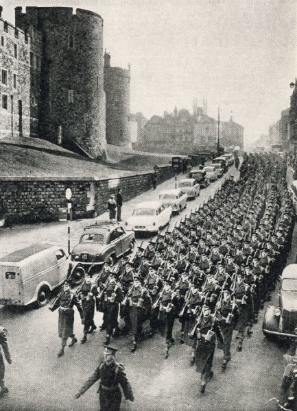 Leaving England for Germany: the 1st battalion, Scots Guards, march past Windsor castle en route to the railway station. On Nov. 14 the 1st Battalion, Scots Guards, left Windsor for Germany, where they were to join the 4th Guards Brigade, near Dusseldorf
