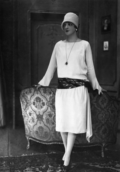 Mlle Jane Renouard in a Jean Lanvin dress: bateau or boat neckline, sleeves with bell shaped tapered cuffs, godet style drapery, sequined sash, a cloche hat & court shoes. Date: late 1920s