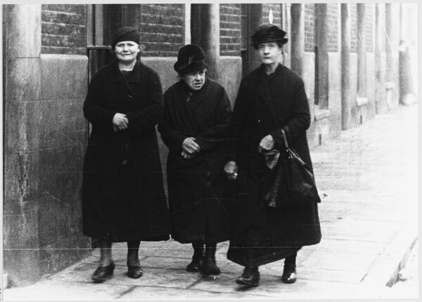 Three working class ladies of advancing years walk down a London street, well wrapped-up against the cold