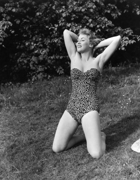 Blonde model poses on the grass in a strapless ocelot / leopard print bathing costume Date: 1950s
