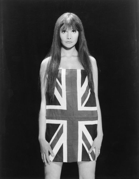 A British model with a fringe & straight dark hair, covers her modesty with the Union (British) flag, as she strikes a pose