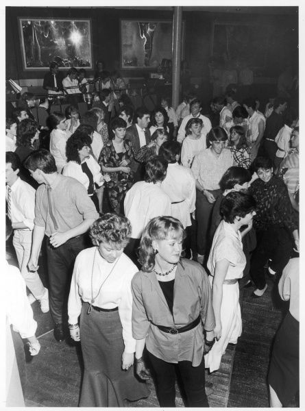 Young people strutting their stuff on the dance floor, wearing various fashions of the day, including shoestring ties and fishnet gloves