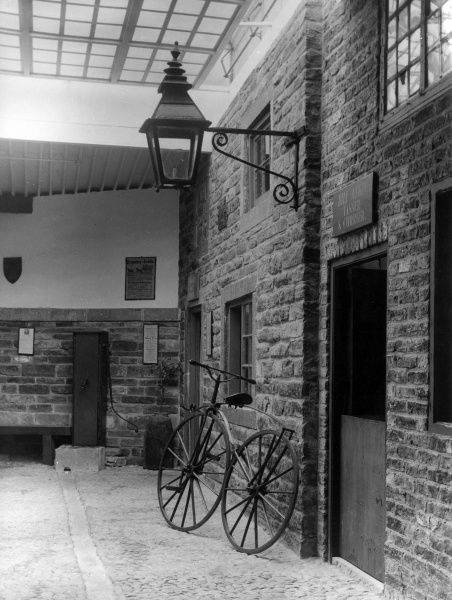'Abbey Fold', a reconstructed early 19th century street, at Kirkstall Abbey House Museum, Leeds, Yorkshire, England. Note the Safety bicycle and water pump. Date: 19th century