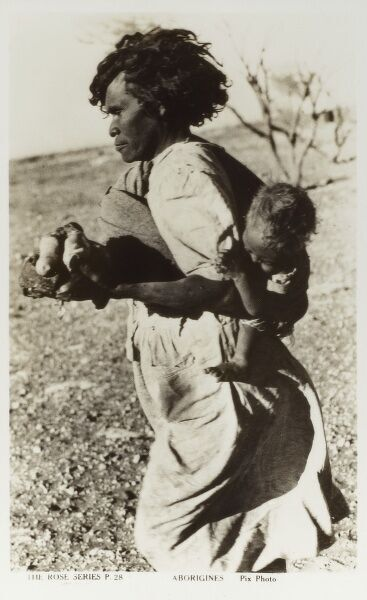 An aboriginal Mother, carrying her baby on her back, taking food obtained from the 'Tea and Sugar' train back to her wurley (a shelter or hut, made of branches and leaves). The Tea and Sugar Train (also known as Slow Mixed Goods Train No