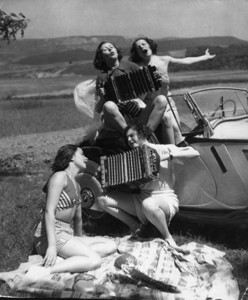 Four crazy girls, singing enthusiasticall to their accordions beside their sports car, in the middle of the countryside! Date: 1930s