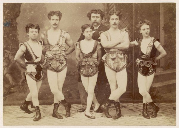5 acrobats, 3 of them boys, pose with legs crossed, with their ?manager. Their costume consists of decorative shorts & leotards with soft lace-up boots or pumps