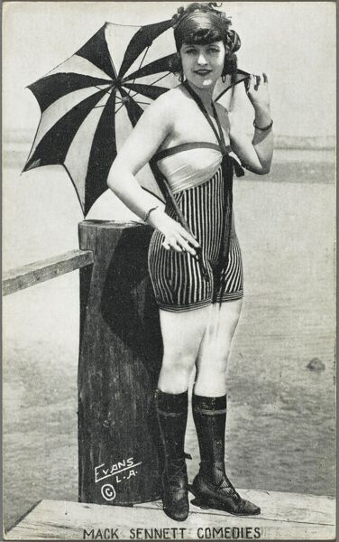 A rather lovely actress in a rather skimpy swimsuit from the Mack Sennett Comedy Studios, Los Angeles, USA. She holds a fine striped parasol and stands at the end of a jetty, perhaps about to jump off in a humourous fashion