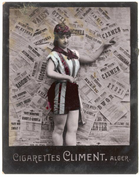 A buxom young woman wearing a pair of shorts with stripes down the sides poses in front of a backdrop of theatre posters from Eastern Europe