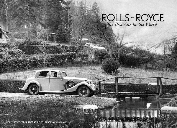 Advertisement for Rolls Royce cars 'the best car in the world'. Photograph of a Rolls Royce being driven by a chauffeur through a pretty rural scene