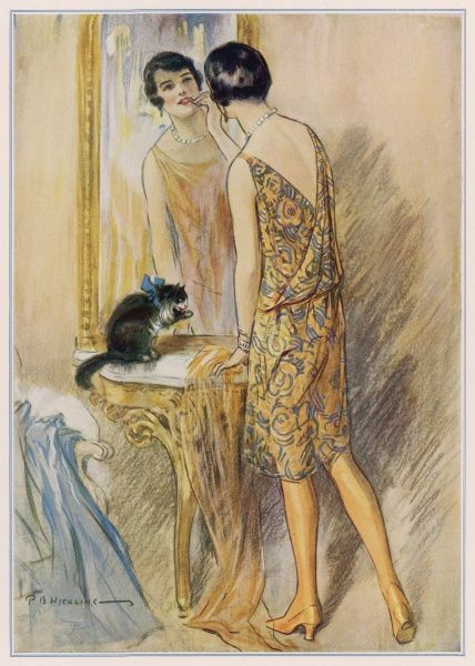A typical 1920s flapper girl, wearing a short dress, yellow stockings and with bobbed, shingled hair, applies her lipstick in the mirror watched by a fairly diffident cat