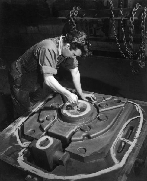 A metalworker makes adjustments to a mould, to be used to shape a metal plate on a large industrial hydraulic press. Photograph by Heinz Zinram