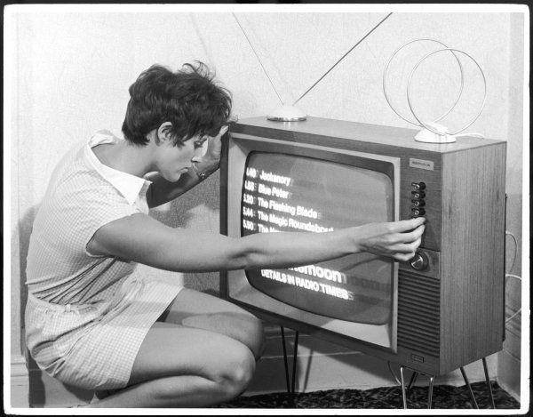 A woman adjusts her TV set which is showing a list of the afternoon's programmes