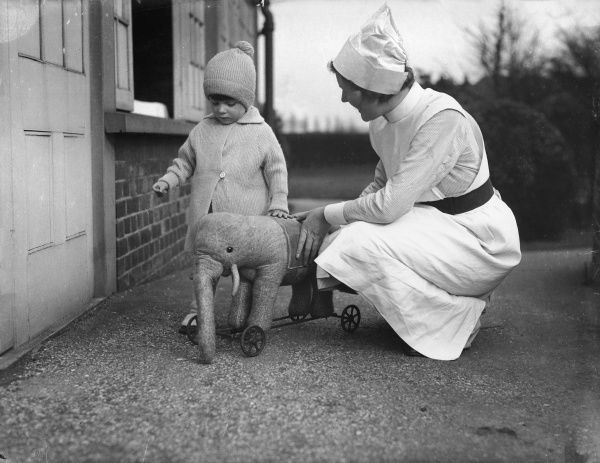 A nurse at the National Adoption Society playing with a little boy in a bobble hat with his toy elephant on wheels