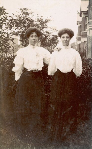 Twin sisters in identical clothes pose in the garden for a photograph