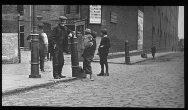 Adults and children on a London street, outside the gates of a large building, possibly a warehouse. One boy, carrying a toddler, has bare feet. An old man leans on a bollard and looks directly at the photographer. A sign lists place names: Cork