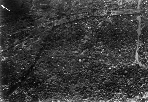 Aerial photograph (German) of a battle area near Verdun, France, showing trenches, mine craters and shell pitted ground during the First World War. Date: circa 1916
