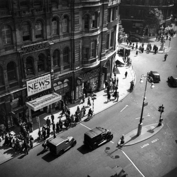 Aerial view of a street near Leicester Square, London, with the Monseigneur News Theatre on the left, and Bravingtons jewellers further along.  circa 1940s