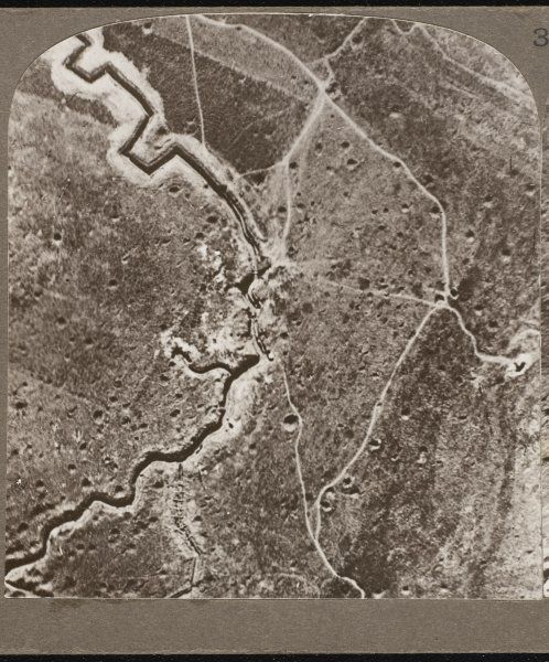 An aerial photograph over the German lines, showing deep trenches, mine craters, and shell-pitted ground