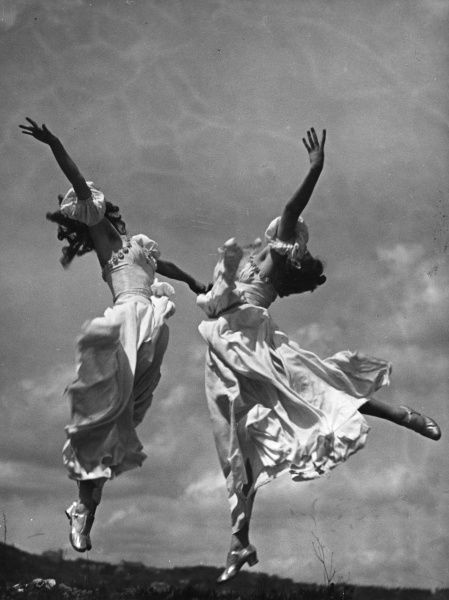 Two girls performing a graceful outdoor dance. Date: 1930s