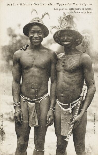 Two native black African men from the Mankaignes Tribe of Senegal smile to show off their sharpened teeth, filed down to points. The gentleman on the right displays traditional body scarification and carries a pipe. Both wear feathered hats