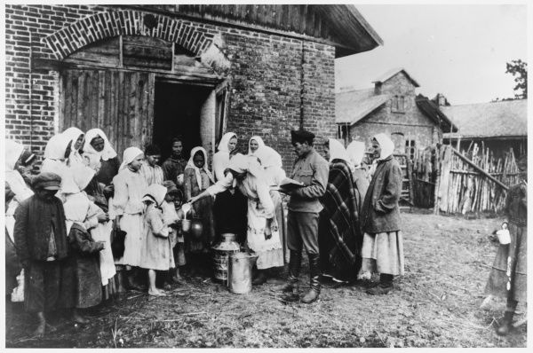 Food distribution in an agricultural commune: women and bare-footed children queue for milk