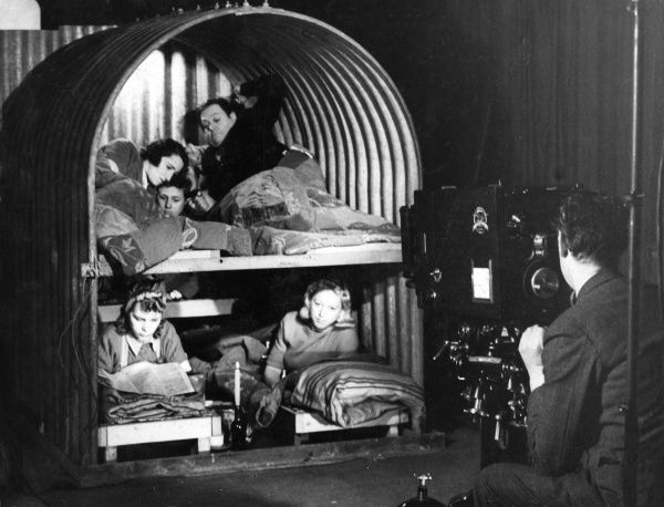 Making a promotional film for the famous Anderson air raid shelter, fitted with bunk beds, so that people could lie down instead of sitting bolt upright during a raid. Date: 1940