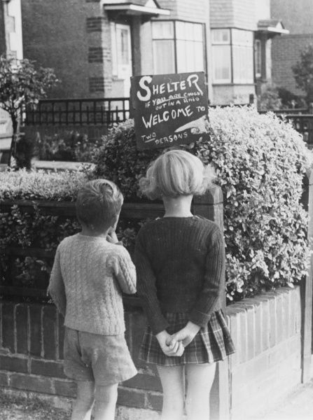 Two children read a sign...'Shelter. If you are caught out in a raid, welcome to two persons', outside a family home