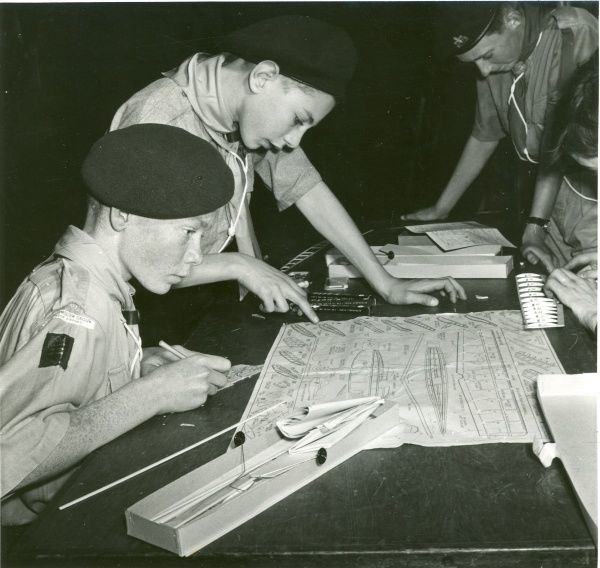 Air Scouts of London Airport Group pore over instructions on a table to build a model aeroplane. circa 1950s