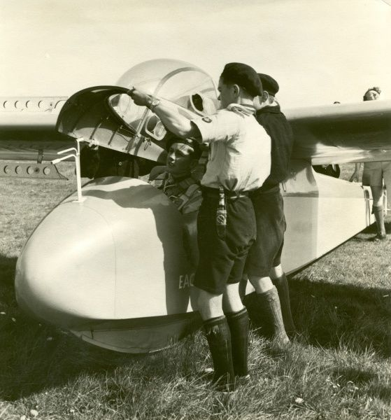 Two Air Scouts lift and place the canopy on a glider with another Scout already in the cockpit. 1958