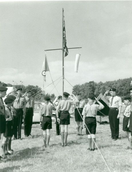 Portsmouth Air Scouts standing in a field saluting a large pole flying the Union Jack and other flags at Flag Break. circa 1950s