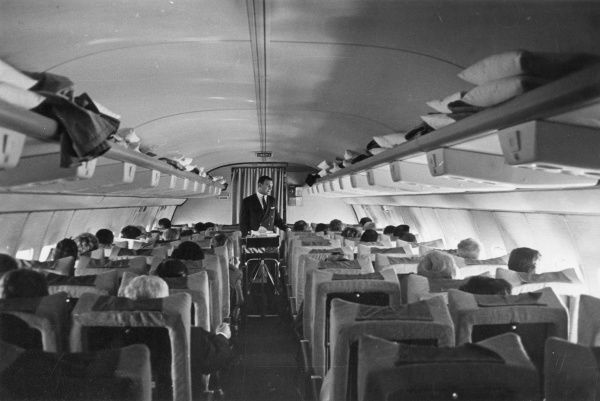 An Air Steward pushes a trolley down the aisle of a Lufthansa Boeing 727 aeroplane, offering passengers light refreshments. Date: late 1960s