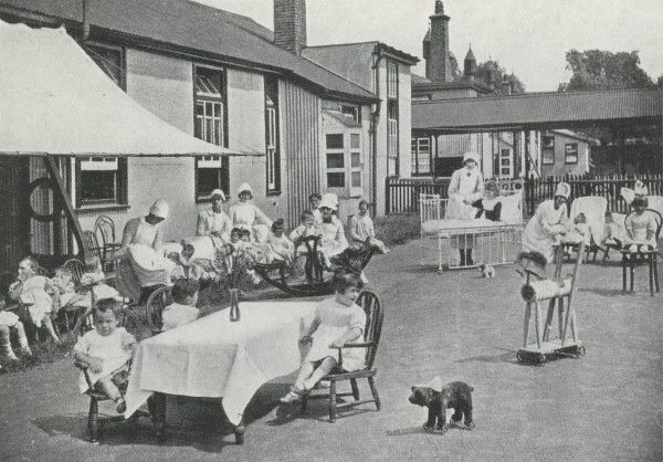 Children and nurses enjoy playing with toys in an 'airing court' at the Fountain Hospital at Tooting in Surrey (now South London)