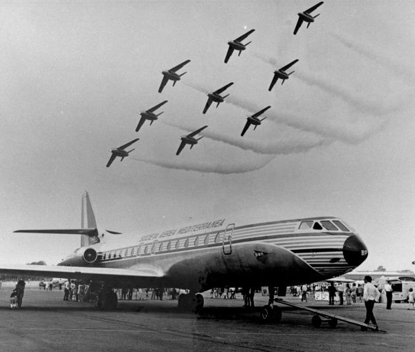 Scene at an airport with a Caravelle jet on the runway, with nine small aeroplanes flying in formation overhead