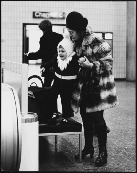 A young mother wearing a fur coat and patent leather platform boots does her best to control her naughty child as it has a tantrum at London Gatwick Airport, England