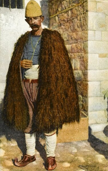 Albanian peasant shepherd wearing a cloak make out of a long-haired goat and traditional footwear of the curled-up and slightly pointy variety
