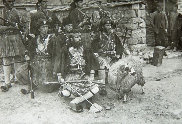 A group of Albanian soldiers in traditional costume, with rifles. Their mascot, a ram, stands alongside