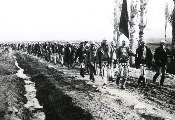 Albanian volunteers with a flag, marching along a road in Serbia on the eastern front during the First World War. Date: 1916