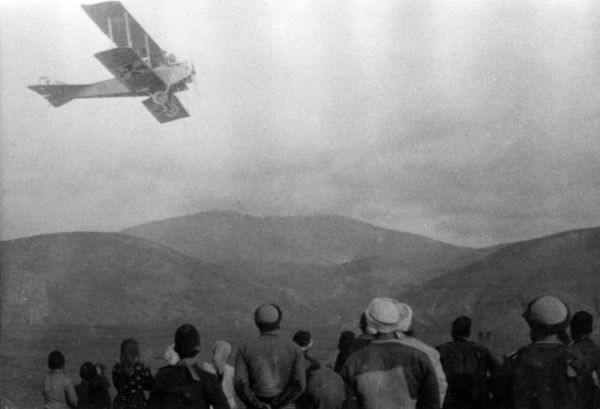 Albanians watching a biplane flying overhead in Serbia during the First World War. Date: 1915