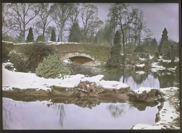 A view of Aldenham House Gardens, near Borehamwood, Hertfordshire, with a scattering of snow. An ivy-covered bridge can be seen, crossing some water