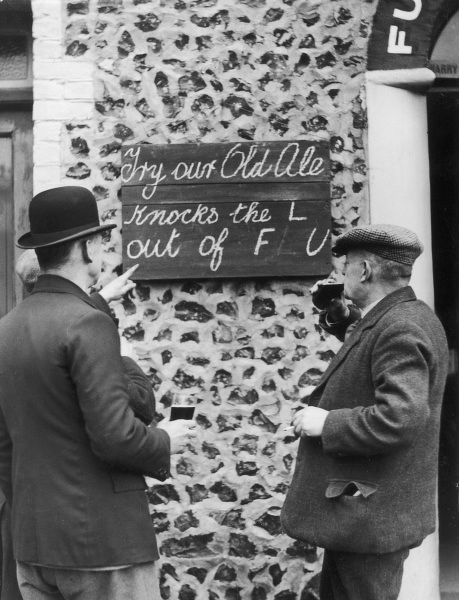Two men, one in a flat cap, the other in a bowler hat, drinking glasses of ale, while looking at the punning pub sign: Try Our Old Ale: knocks the L out of FLU