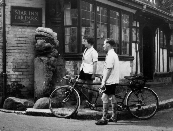 Cyclists admire a grotesque figure outside the 'Star Inn'. at Alfriston, Sussex, England. Known as the 'Alfriston Lion', it was once the figurehead of a Dutch warship. Date: August 1940